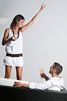 Young woman with white wine standing next to couch with young man and wine