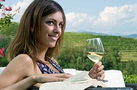 Young woman sitting in vineyard with white wine and a book
