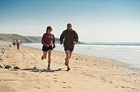 A couple jogging running on Newgale Beach, Pembrokeshire Coast National Park, warm spring afternon, Wales UK