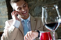 Young man in suit with mobile phone at a restaurant checking time (thumbnail)