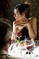 Young woman sitting at restaurant table with young man