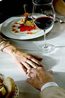 Closeup of couple's hands touching at dinner table