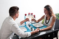 Couple sitting at table toasting with white wine and holding hands