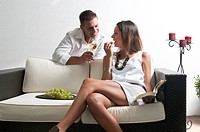 Young man leaning on couch with white wine and young woman reading book and eating grapes