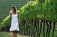 Young woman in vineyard sniffing wine glass (thumbnail)