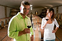 Couple in a wine cellar with glasses of red wine
