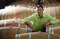 Young man in wine cellar with wooden barrels