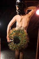 Rear view of a woman holding a peacock feather fan and posing