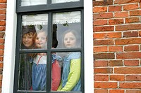 Boy with his two sisters looking through a window