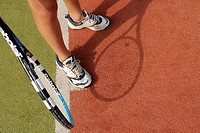 Low section view of a person with a tennis racket