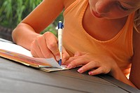 Close_up of a girl writing on a sheet of paper