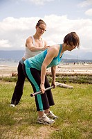 Instructor and woman practicing yoga on beach, Vancouver, BC