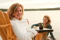 Woman in deck chair smiling at camera, second woman seated on dock, Clear Lake, Manitoba, Canada
