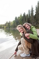 Two women embrace at shoreline, Clear Lake, Manitoba, Canada