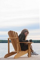Woman dialing on cellphone, seated in deck chair on dock, Clear Lake, Manitoba, Canada