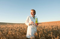 Woman holding flask and clipboard in field of grain, Manitoba, Canada