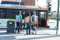 Group of teens walking toward transit bus, Winnipeg, Manitoba, Canada
