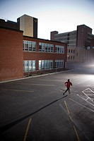Runner sprinting in urban parking lot, morning, Regina, Saskatchewan