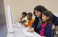 teacher helping student on the computer