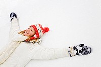 winter scene: blond girl laying down on the snow. Copy space on the right side