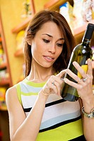 woman in a supermarket reading the label behind a bottle of wine
