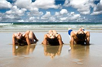 Three best friends seated on the sand having fun on the beach