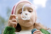 The little girl starts up soap bubbles close upThe little girl starts up soap bubbles close up