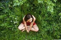 The top view on the girl_teenager sitting on a green grassThe top view on the girl_teenager sitting on a green grass