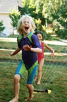 Girls Laughing and Running Through Sprinkler