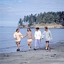 Two Couples Walking Along A Beach