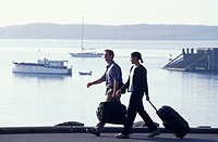 Travelers Walking With Suitcases Along The Harbor