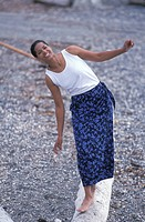 Smiling African American Woman Standing On A Log On A Rocky Beach