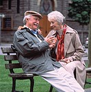 Elderly Couple Sitting On Park Bench And Smiling