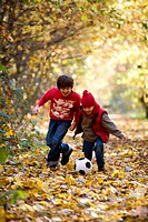 Boys playing with a soccer ball in a park