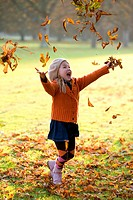 Girl tossing dry leaves in the air
