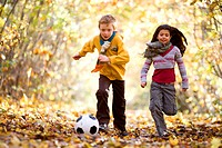 Boy and girl playing with a soccer ball in a park