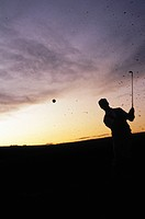 Silhouette of a man playing golf