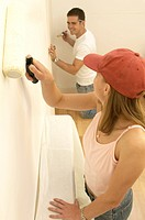 Side profile of a young couple painting a wall (thumbnail)