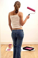 Rear view of a young woman holding a roller brush