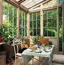 A dining table laid out in a greenhouse