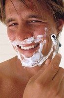 Close_up of a mid adult man shaving his face