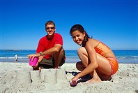 Portrait of a father and his daughter making sand castles on the beach