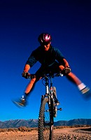 young man doing tricks on a mountain bike