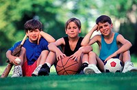 boys sitting with assorted sports items