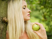woman eating apple while leaning against tree