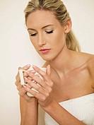woman in bath robe holding mug of tea