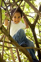 cute boy climbing a tree and smiling