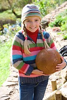Smiling girl holding soccer ball outdoors