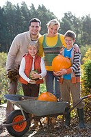 Smiling family with autumn pumpkins and wheelbarrow outdoors