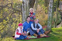 Mother, father and daughters having picnic outdoors